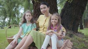Rijpe vrouwenzitting op het gras onder de boom in het park met twee leuke in camera en kleindochters die, die kijken glimlachen stock videobeelden