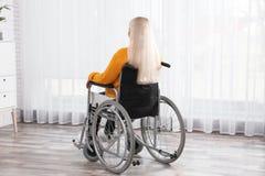 Rijpe vrouwenzitting in rolstoel dichtbij venster royalty-vrije stock fotografie