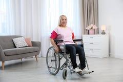 Rijpe vrouwenzitting in rolstoel stock foto