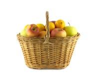 Rijpe vruchten en appelen in rieten mand  Stock Fotografie