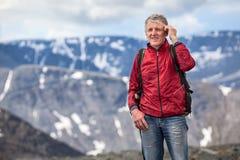 Rijpe wandelaar die op mobiele telefoon spreken en camera op hoogte van berg bekijken Stock Foto's