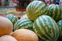 Rijpe watermeloenen en meloenen bij de seizoengebonden markt stock foto