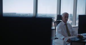 Rijpe zakenman die bij zijn bureau werken stock videobeelden