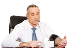 Rijpe zakenman die bloeddruk meten Stock Afbeeldingen