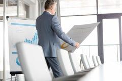 Rijpe zakenman die grafiek op grafiek in raadsruimte analyseren Stock Foto