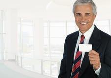 Rijpe zakenman die in hoog zeer belangrijk bureau het houden van een leeg adreskaartje plaatsen royalty-vrije stock afbeelding