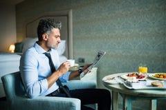 Rijpe zakenman die ontbijt in een hotelruimte hebben Royalty-vrije Stock Afbeeldingen