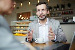 Rijpe Zakenman Discussing Work op Vergadering in Koffie stock foto's