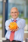 Rijpe Zakenman Holding Piggy Bank in Bureau Stock Foto's