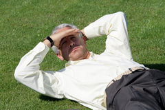 Rijpe zakenman op gras Stock Foto's
