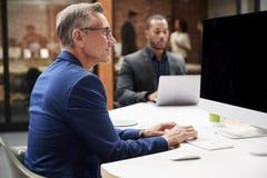 Rijpe Zakenman Working At Desk op Computer in Open Planbureau met Collega's op Achtergrond royalty-vrije stock afbeeldingen