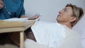 Rijpen de verpleegsters voedende gehandicapten vrouw met havermoutpap, zorg voor patiënten, armenhuis stock videobeelden