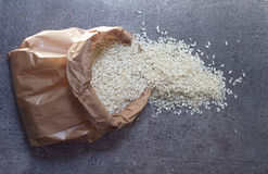 Rijst in document pak op steenachtergrond stock foto