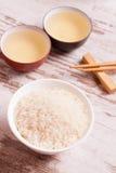 Rijst, groene thee en eetstokjes voor sushi op witte houten backgro stock afbeeldingen