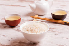 Rijst, groene thee en eetstokjes voor sushi op witte houten backgro stock fotografie