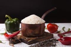 Rijst in ijzer stewpan met groenten op houten scherpe plank Zwarte achtergrond Royalty-vrije Stock Afbeelding