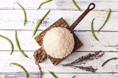 Rijst in ijzer stewpan met slabonen op houten scherpe plank, hoogste mening Stock Fotografie