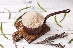 Rijst in ijzer stewpan met slabonen op houten scherpe plank Witte achtergrond Royalty-vrije Stock Foto