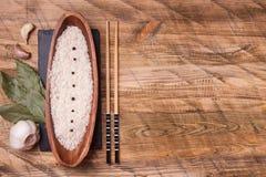 Rijst in kom met knoflook en laurierblad, hoogste mening Stock Foto's