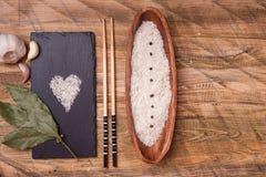 Rijst in kom met knoflook en laurierblad, hoogste mening Royalty-vrije Stock Foto