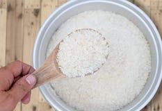 Rijst in kooktoestelpot met houten lepel Stock Foto's