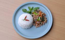 Rijst met be*wegen-gebraden varkensvlees en basilicum wordt bedekt dat Stock Fotografie