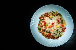 Rijst met gemengde groenten op witte plaat op donkere houten achtergrond Royalty-vrije Stock Foto