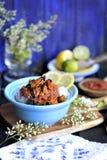 Rijst met zeevruchten, in tomatensaus Met citroen en kalk Voor een blauwe houten die achtergrond, met een boeket van de lente wor royalty-vrije stock afbeelding