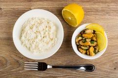 Rijst in plaat, de helft van citroen, mosselen met peterselie in kom, vork op lijst Hoogste mening stock afbeeldingen