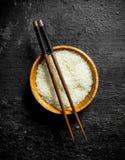 Rijst voor sushi in een houten plaat met stokken stock foto
