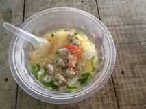 Rijstcongee mengde zich met garnalen, pijlinktvis en varkensvlees in plastic kom en lepel stock afbeelding