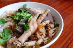 Rijstnoedels met kruidige varkensvleessaus en Kippenvoet Stock Afbeeldingen
