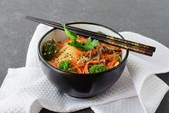 Rijstnoedels met wortel, broccoli en paddestoelen in een zwarte kom op een zwarte abstracte achtergrond Aziatisch Voedsel Gezond Stock Foto's