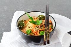 Rijstnoedels met wortel, broccoli en paddestoelen in een zwarte kom op een zwarte abstracte achtergrond Aziatisch Voedsel Gezond Stock Foto