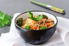 Rijstnoedels met wortel, broccoli en paddestoelen in een zwarte kom op een zwarte abstracte achtergrond Aziatisch Voedsel Gezond Royalty-vrije Stock Afbeelding
