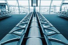 Rijzetels voor passagiers in de luchthavenhal Op de achtergrond Stock Foto