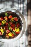 Rik chokladkaka med jordgubbar och ätliga blommor i en trädgård - sommarlynne Royaltyfria Foton