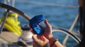 Rik dyr vit guld- cirkel för närbild med den enorma diamanten i blå ask i kvinnliga händer