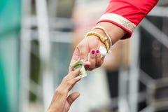 Rik kvinna med det guld- armbandet som ger pengar till en man Royaltyfri Fotografi
