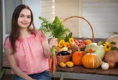 Rik skörd för odlare av grönsaker, enorm harve för trevlig flickaträdgårdsmästare Arkivbild
