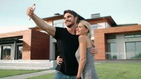Rika par som omfamnar nära lyxiga lägenheter Selfie stående av lyckliga par lager videofilmer
