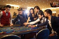Rika vänner gör vad som gambiling på rouletttabellen i kasinot royaltyfria foton