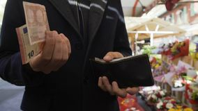Rikeman som ger pengar till den fattiga tiggaren som sölar på blommamarknaden som frågar för allmosa stock video