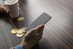 Rikeman som rymmer ett bitcoinmynt och dricker ett kaffe med en telefon, och guld- mynt av bitcoin på en tabell Vinst från arkivfoto