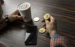 Rikeman som rymmer ett bitcoinmynt och dricker ett kaffe med en telefon, och guld- mynt av bitcoin på en tabell Vinst från arkivbild