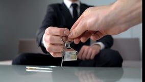 Rikeman som tar tangenter från fastighetsmäklare, den köpande nya lägenheten eller kontor arkivfoto
