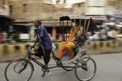 Rikscha-Fahrer-und Passagier-Geschwindigkeit vorüber stockfoto