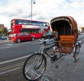 Rikscha und ein roter Doppeldeckerbus in London Lizenzfreies Stockfoto