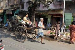 Rikschafahrer, der in Kolkata arbeitet Lizenzfreie Stockfotos