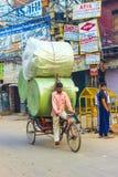 Rikschareiter transportiert schweres Stockbild